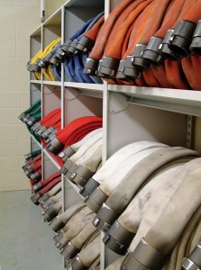 Close up angle of fire hoses stored in shelving units